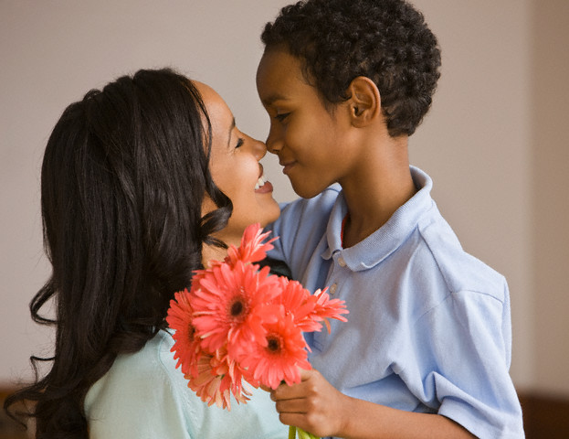 Mixed race boy giving mother bouquet